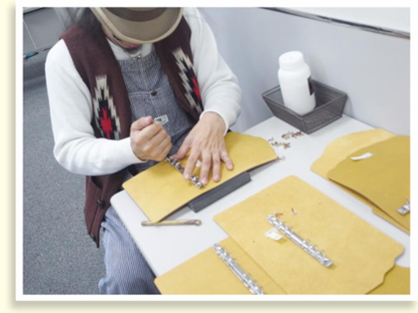 みなさんが縫っている間に、坪谷さんは表紙のカバーにコンチョでバインダーをつけます。この作業、みなさんに体験してもらう予定でしたが、意外と力が必要ということで・・・急遽、坪谷さんにお願いすることになりました。