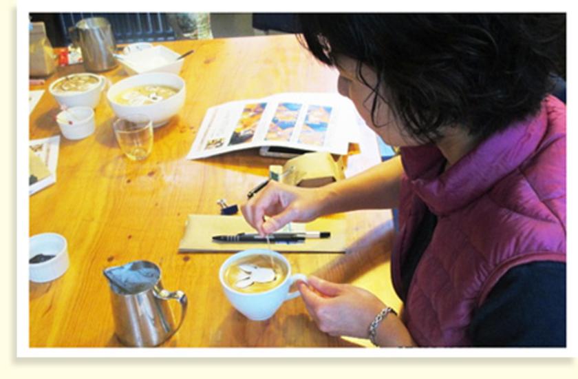 ミルクピッチャーに残ったミルクをスプーンでのせて、絵を描くベースをつくります。さらに、カクテルピンにチョコレートソースやストロベリーソースをつけて自由に描いていくと・・・