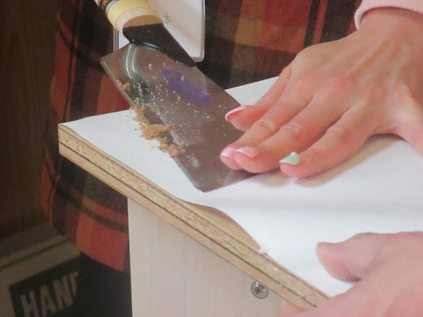 木栓を埋め込んだら、はみ出している部分をノコギリでカット。紙をあてて、天板にキズがつくのを防ぎます。